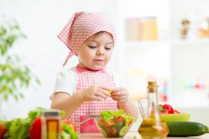 cook kid girl preparing healthy food vegetables